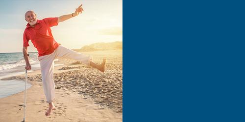 Mann am Strand macht einen Sprung trotz Krücke – Osteopathie in Flensburg