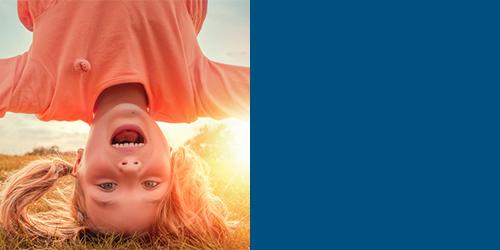 Lachendes Mädchen macht einen Kopfstand – Kinder-Osteopathie