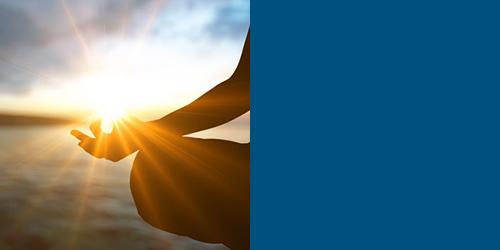 Person meditiert vor untergehender Sonne – Einheit von Körper, Seele und Geist