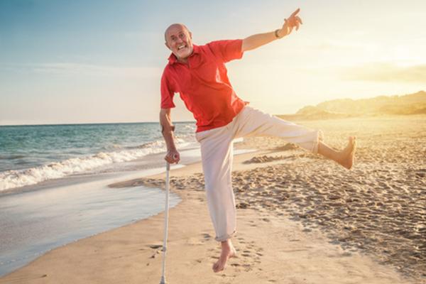 Mann am Strand stützt sich auf seine Krücke und vollführt eine Art Sprung