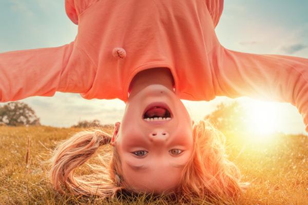 Mädchen mache einen Kopfstand auf der Wiese und lacht