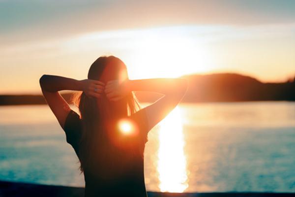 Frau schaut über einen See in den Sonnenuntergang